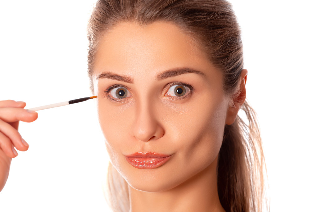 Portrait of beautiful woman with makeup brush
