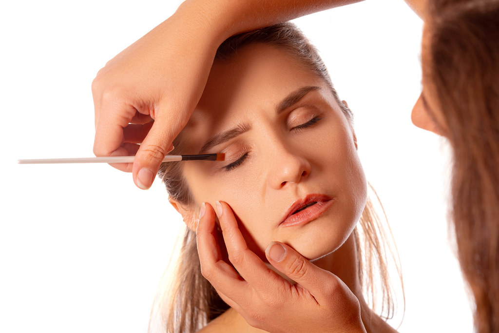 Applying eye makeup products on woman's face