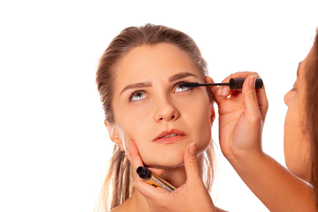 Applying mascara to a woman's eyelashes