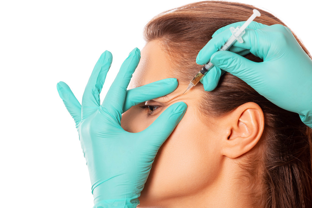 The doctor cosmetologist makes injection procedure for tightening and smoothing wrinkles on the face skin of a beautiful woman