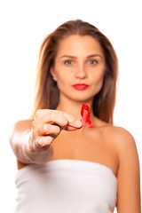 A young woman holds a red awareness ribbon in her hand