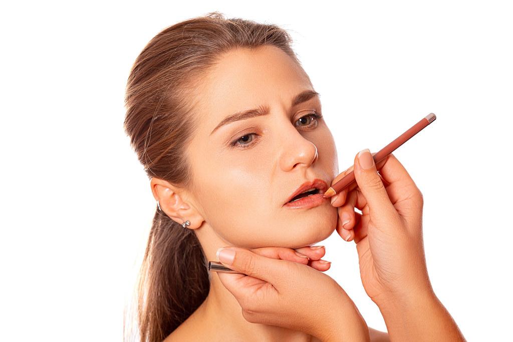 Makeup artist paints lips with lip pencil
