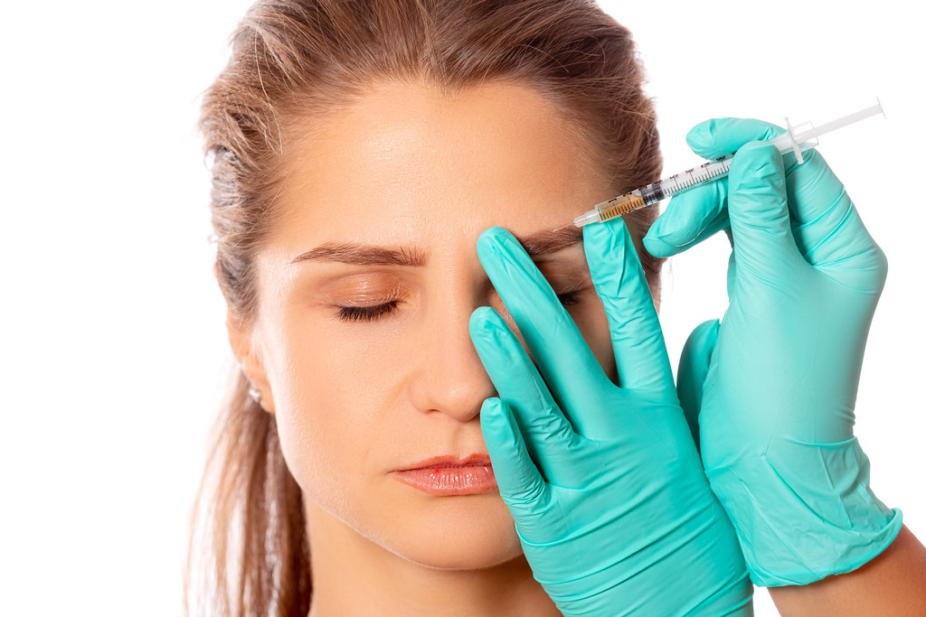 Doctor's hands in gloves make an injection into the eyebrow of a girl