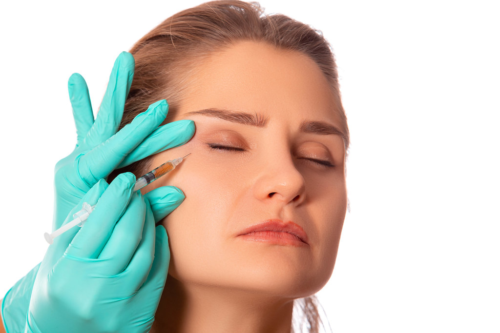 Portrait of attractive young woman getting cosmetic injection
