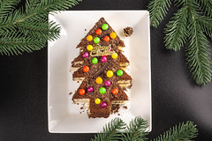 Christmas background with chocolate cake and Christmas tree branches