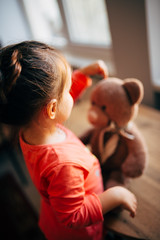 Young girl playing with a stuffed teddy bear.