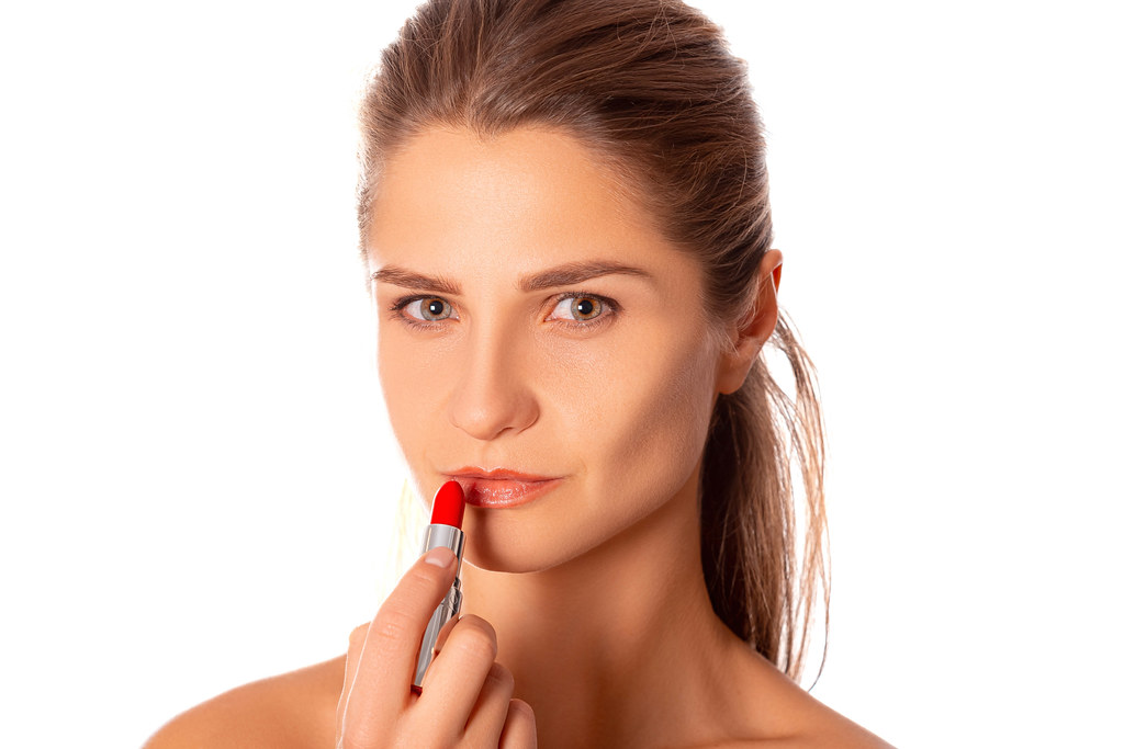 Makeup concept, woman holds red lipstick in hand near lips