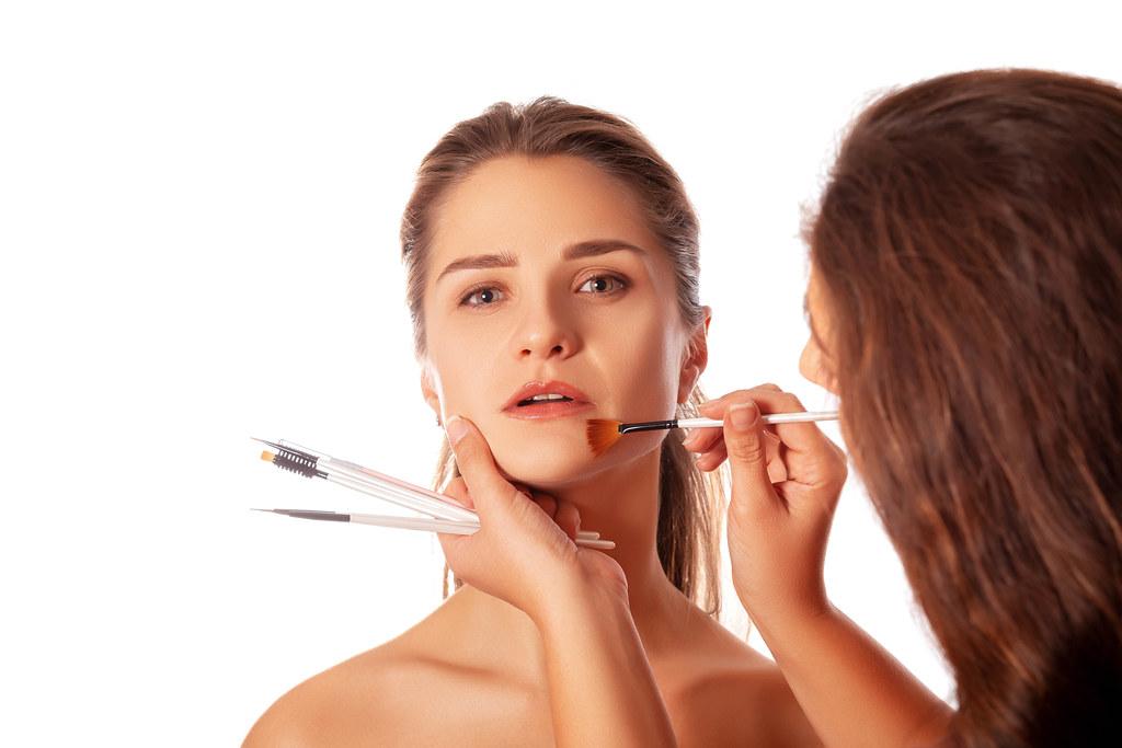 Young beautiful woman applying makeup by makeup artist