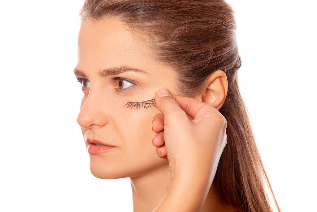 False eyelashes in hand near the girl's face