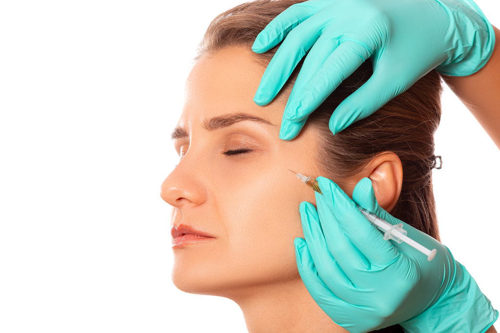 Doctor does injection young woman's face