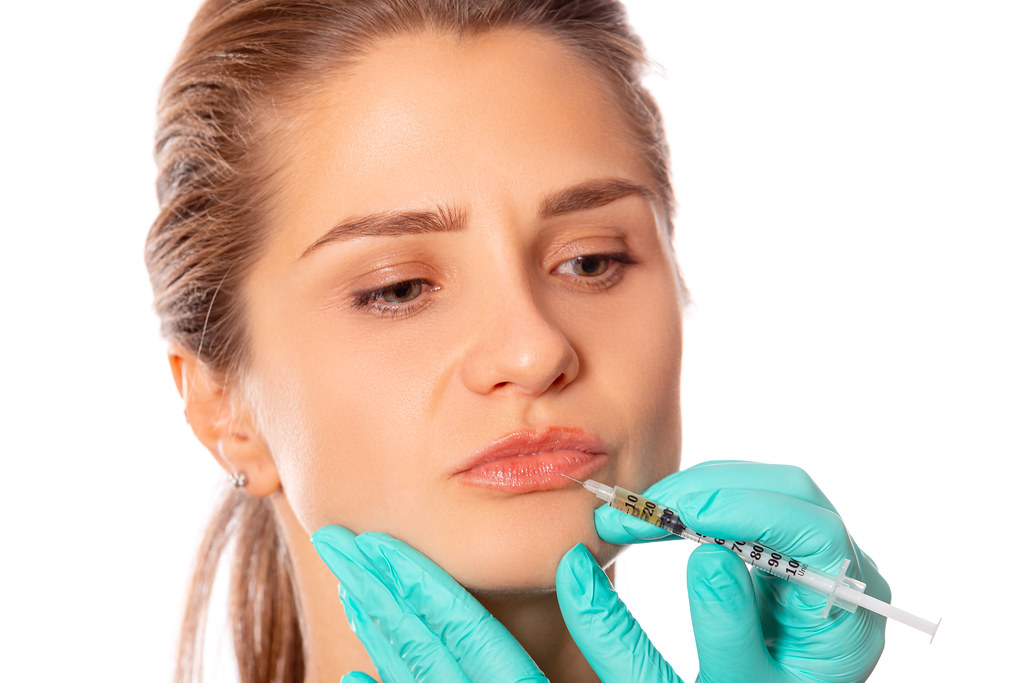 Close-up of a girl's lips and a syringe for injection