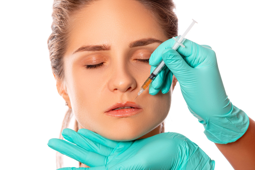 Woman's face and doctor's hands in gloves make an injection above the lip