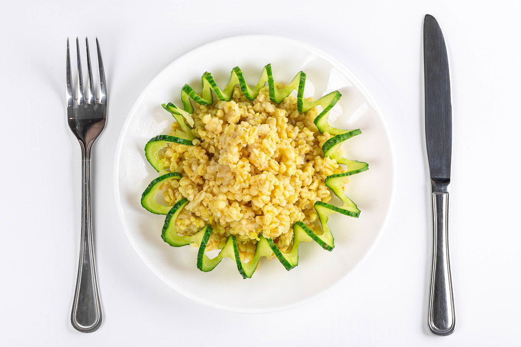 Top view, bulgur porridge with cucumber spiral