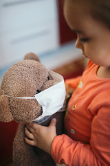 Young girl puttign a face mask on a teddy bear.