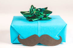 Gift blue box with green bow and black mustache