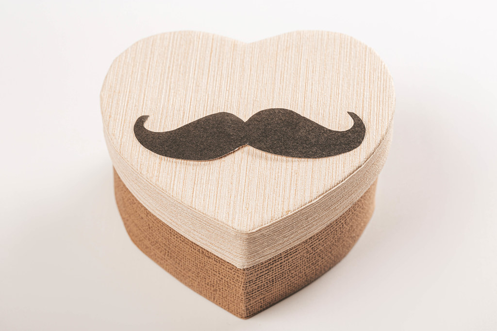 Heart shaped gift box with mustache - happy father's day or birthday greeting concept