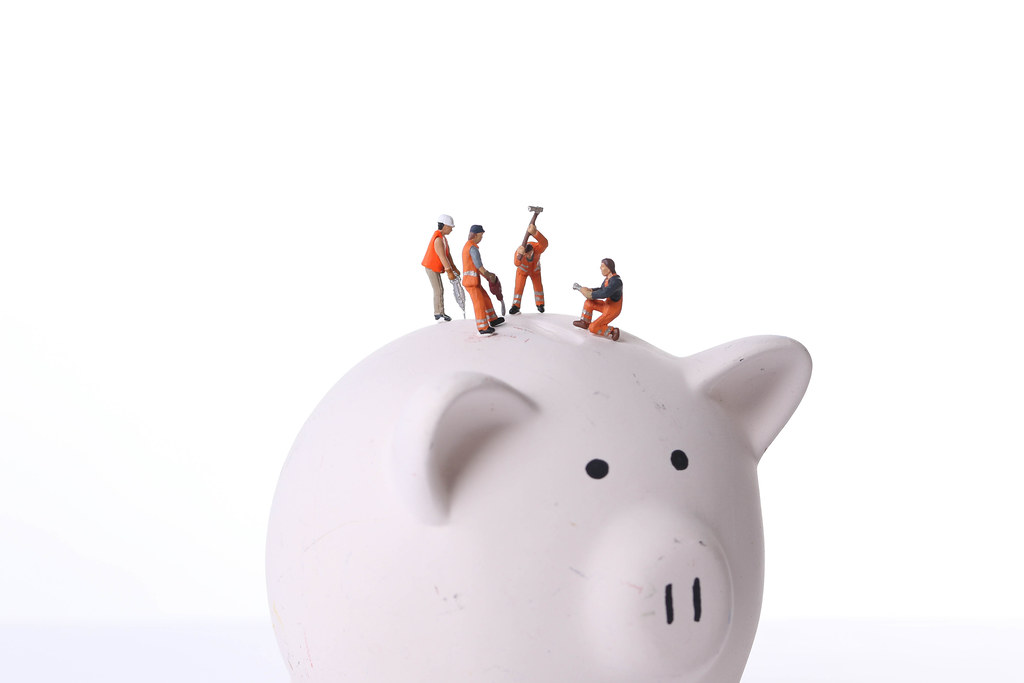 Group of miniature workers working on top of piggy bank