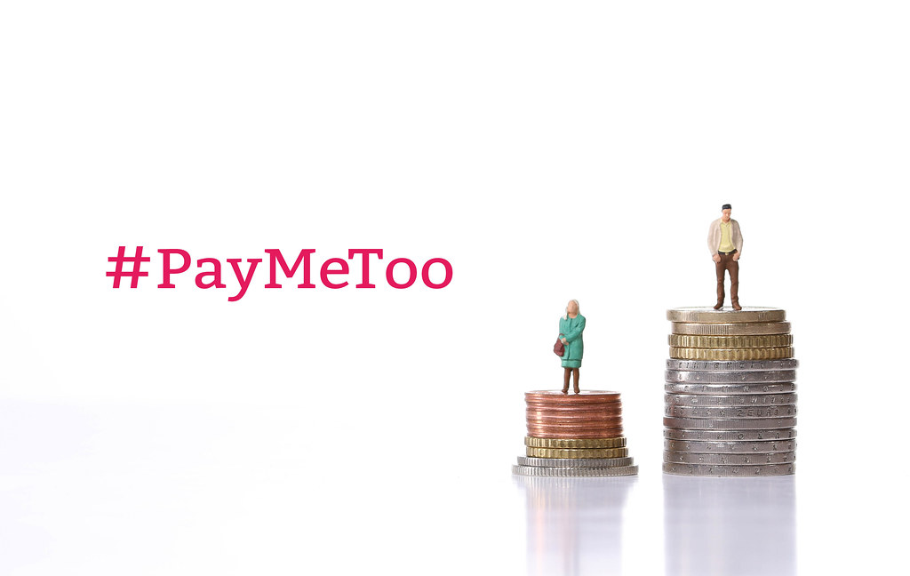 Man and woman standing on a stacks of coins with #PayMeToo text