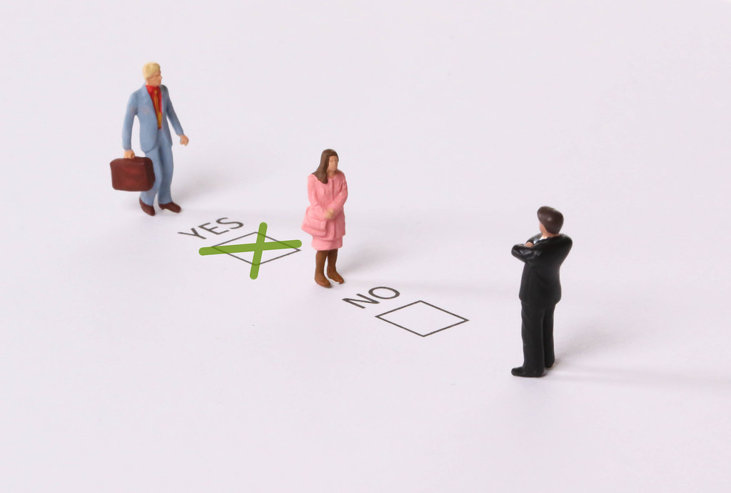 Man and Woman with Yes and No check boxes with green check mark in the Yes box