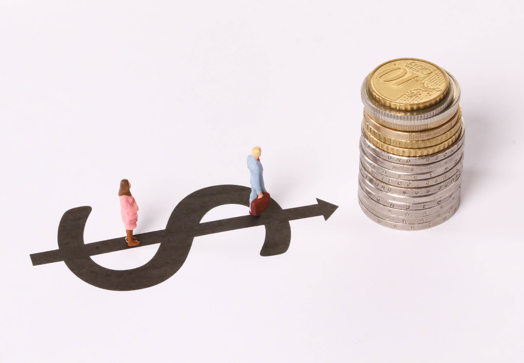 Man and Woman standing on dollar symbol pointing at stack of coins on white background