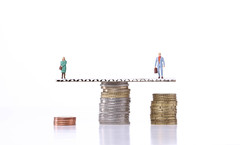 The concept of gender pay gap. Miniature people with stack of coins.