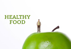 Man with green apple and Healthy Food text