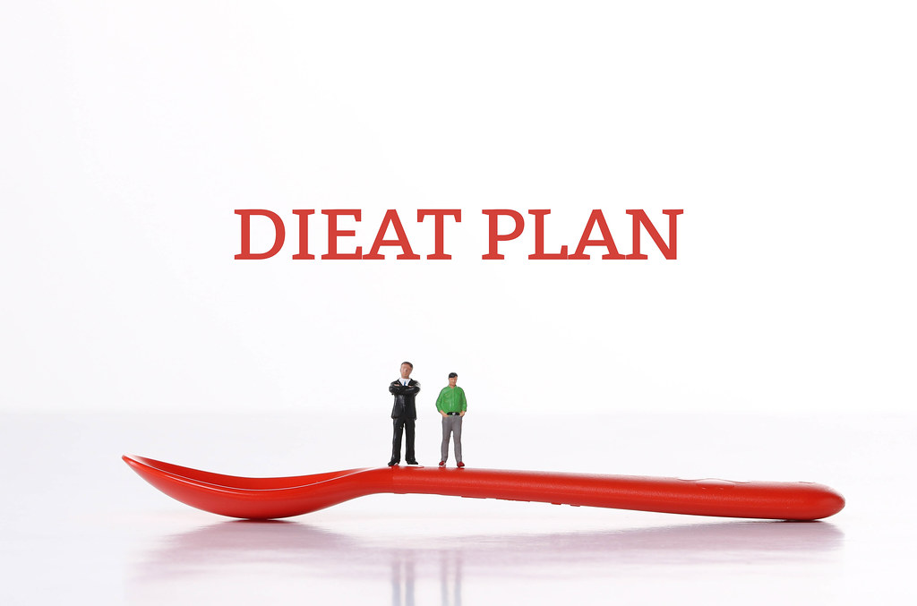 Two men standing on a red spoon and Diet Plan text