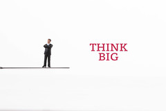 Businessman standing on knife with Think Big text