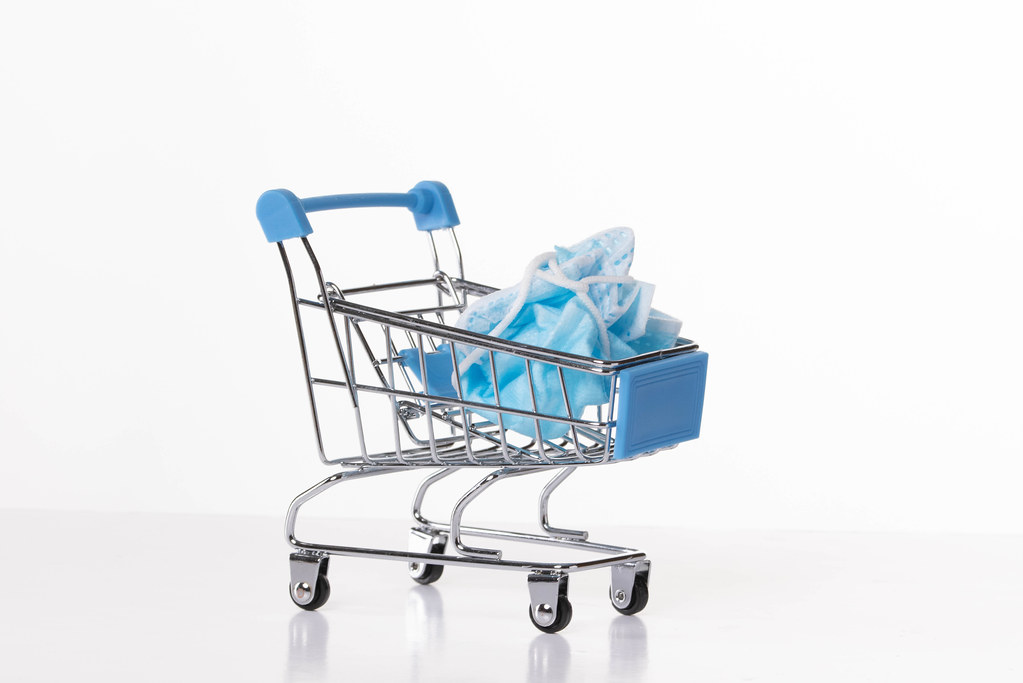 Shopping cart with used medical face mask