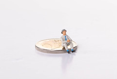 Older man sitting 2 Euro coin