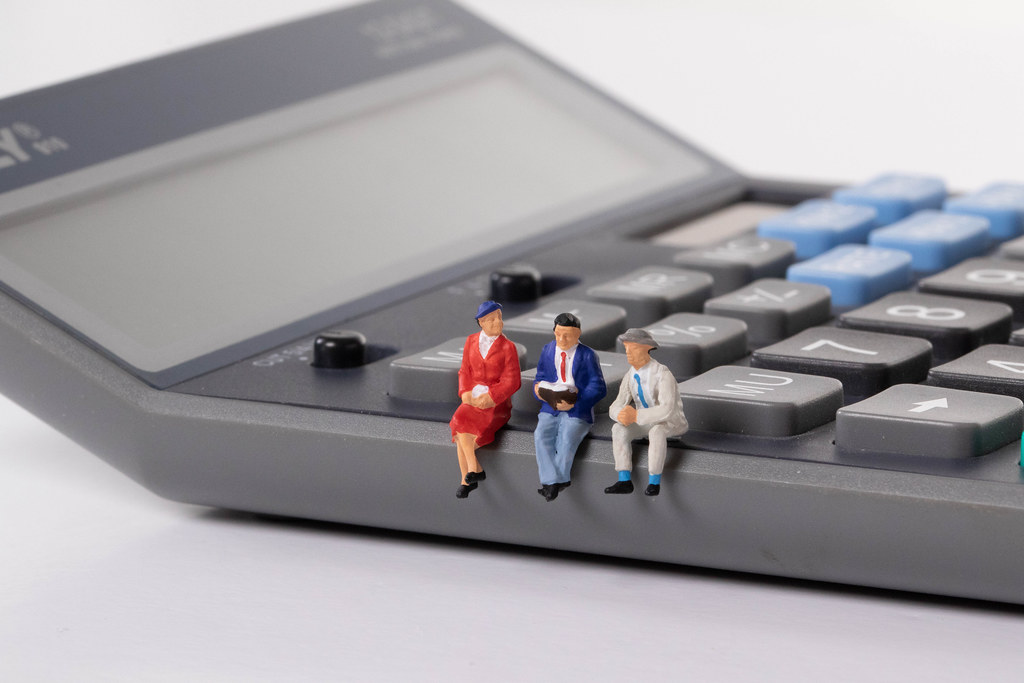 Group of people sitting on calculator