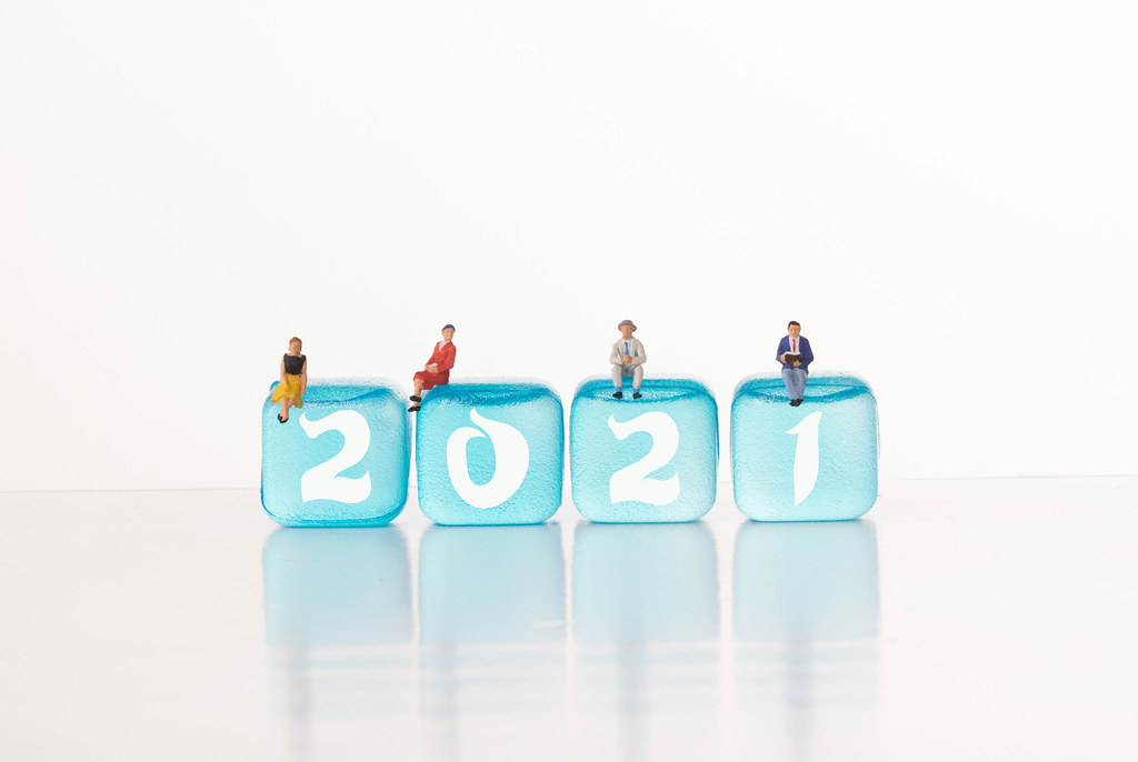 People sitting on blue ice cubes with 2021 text