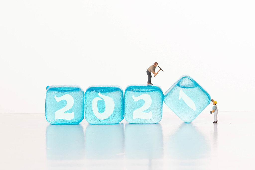 Two workers and blue ice cubes with 2021 text