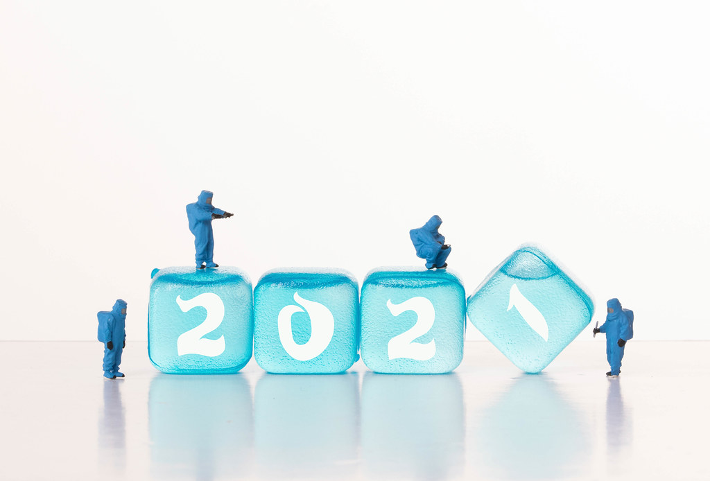 Workers in chemical protection clothes with ice cubes with 2021 text