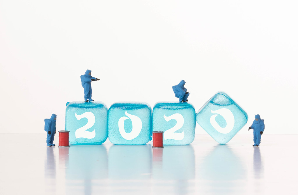 Workers in chemical protection clothes with ice cubes with 2020 text