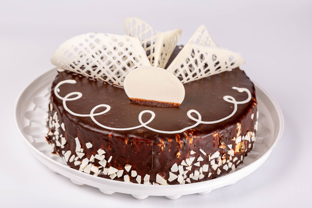 Whole brown chocolate cake with white chocolate decor