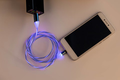 The smartphone is connected to a charger with a glowing cable