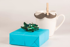 Happy fathers day concept- cup with moustache and blue gift box