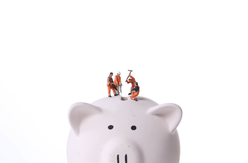 Group of miniature workers on top of piggy bank