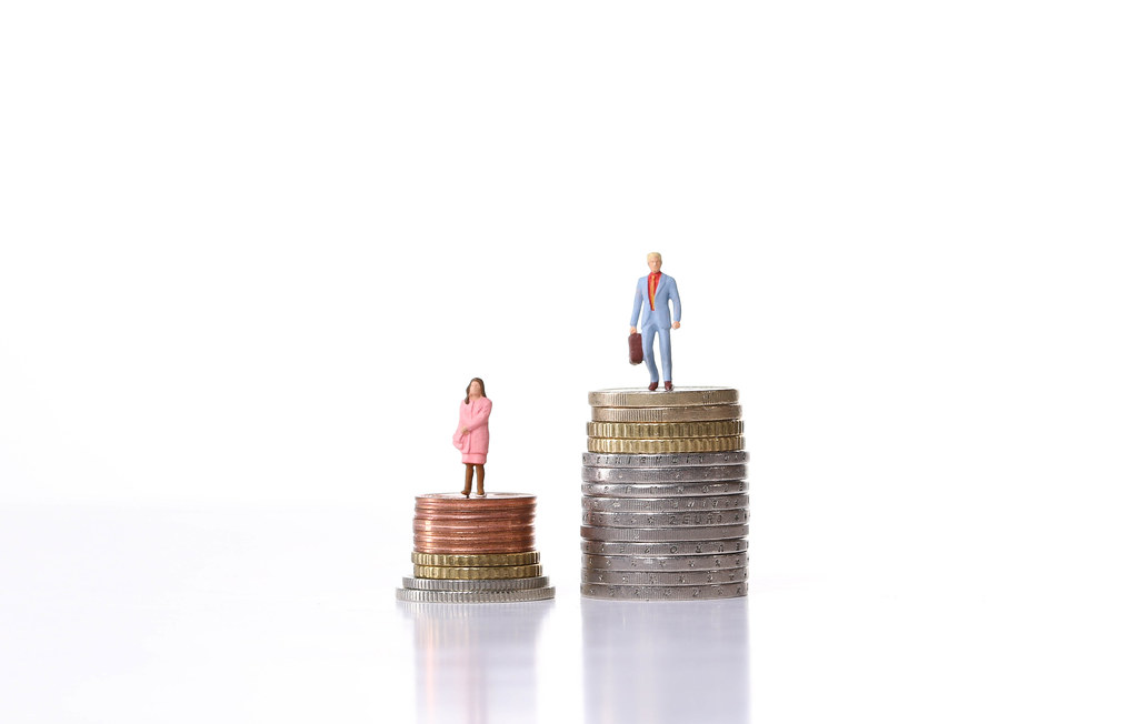 Man and woman standing on a stacks of coins with white background