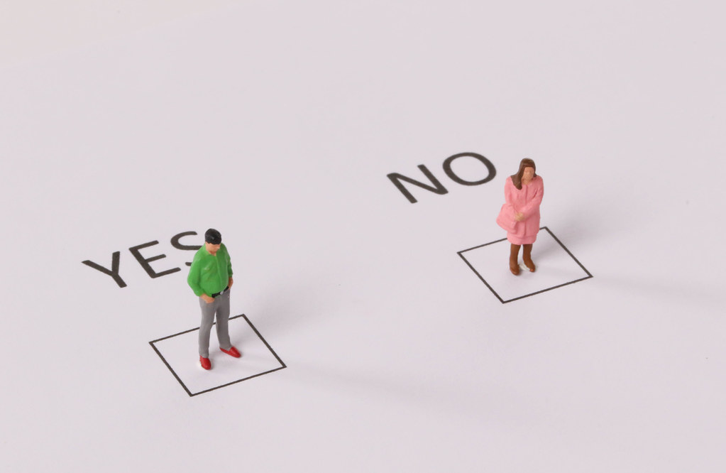 Man and woman standing in a Yes and No checkboxes