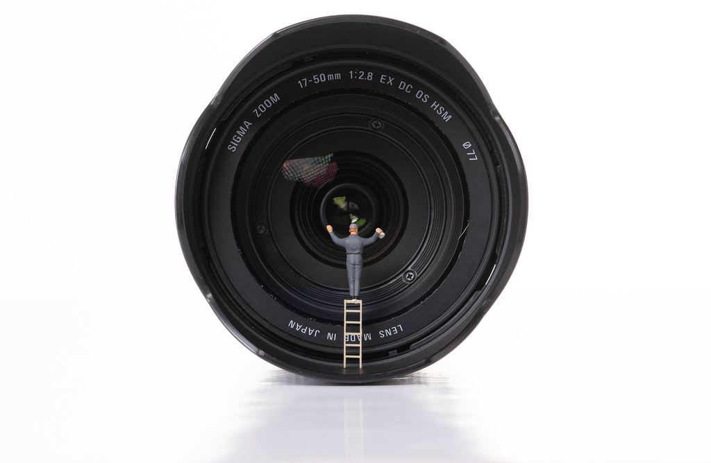 Man cleaning camera lens on white background