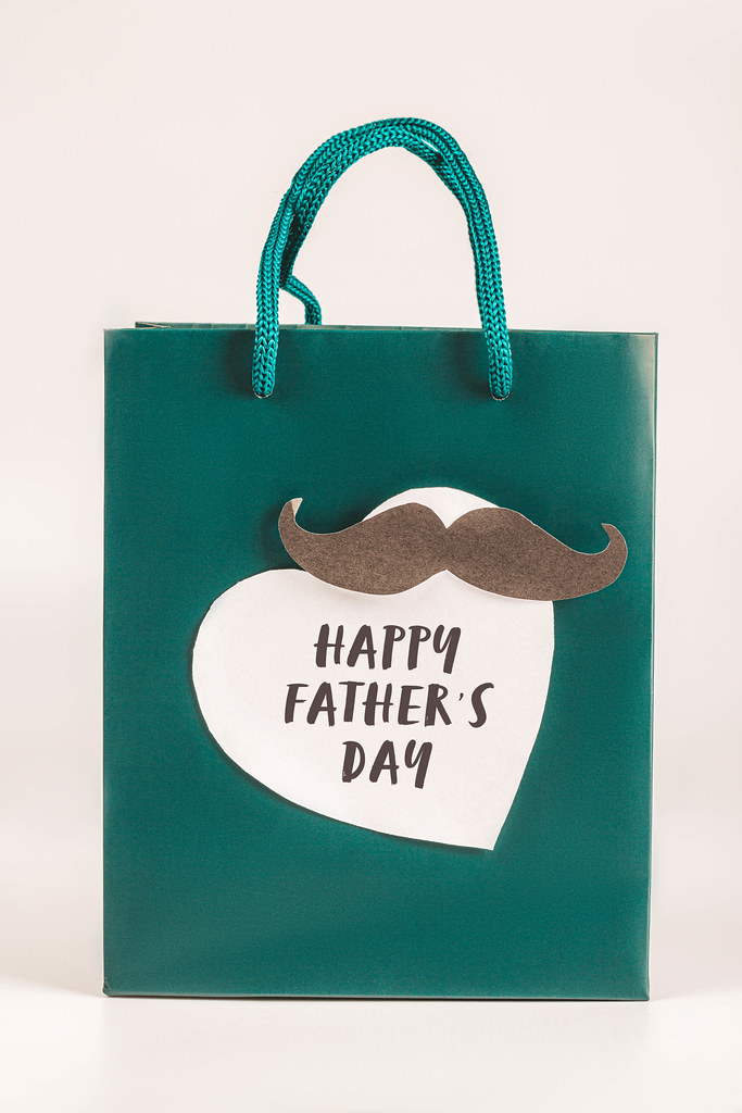 Green gift bag decorated with heart and mustache - father congratulation concept
