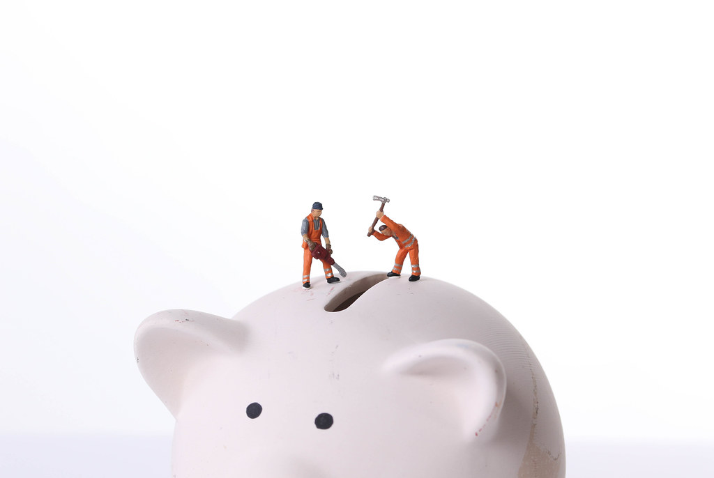 Two miniature workers on top of piggy bank