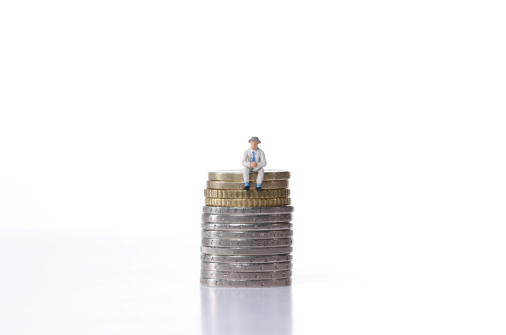 Older man sitting on a stack of coins on white background