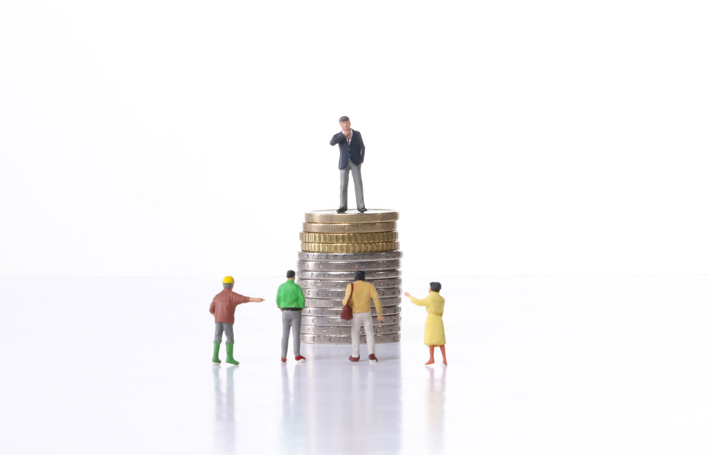 Businessman standing on a stack of coins in front of group of people