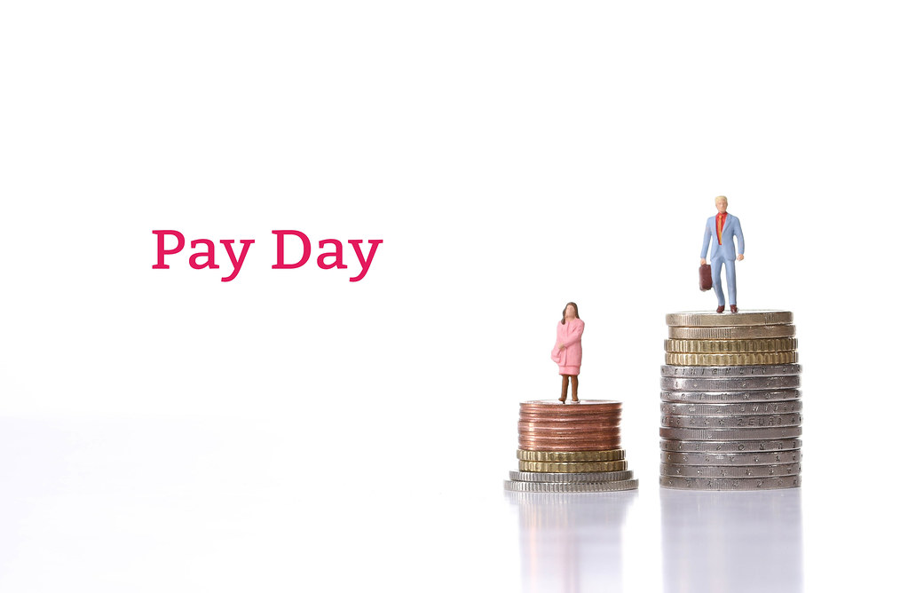Man and woman standing on a stacks of coins with Pay Day text