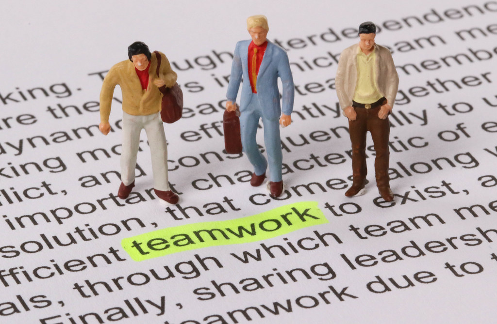 Group of miniature man standing next to a word teamwork highlighted in yellow