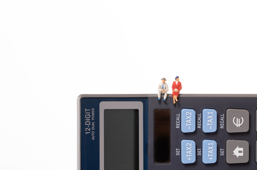 Man and woman sitting on calculator