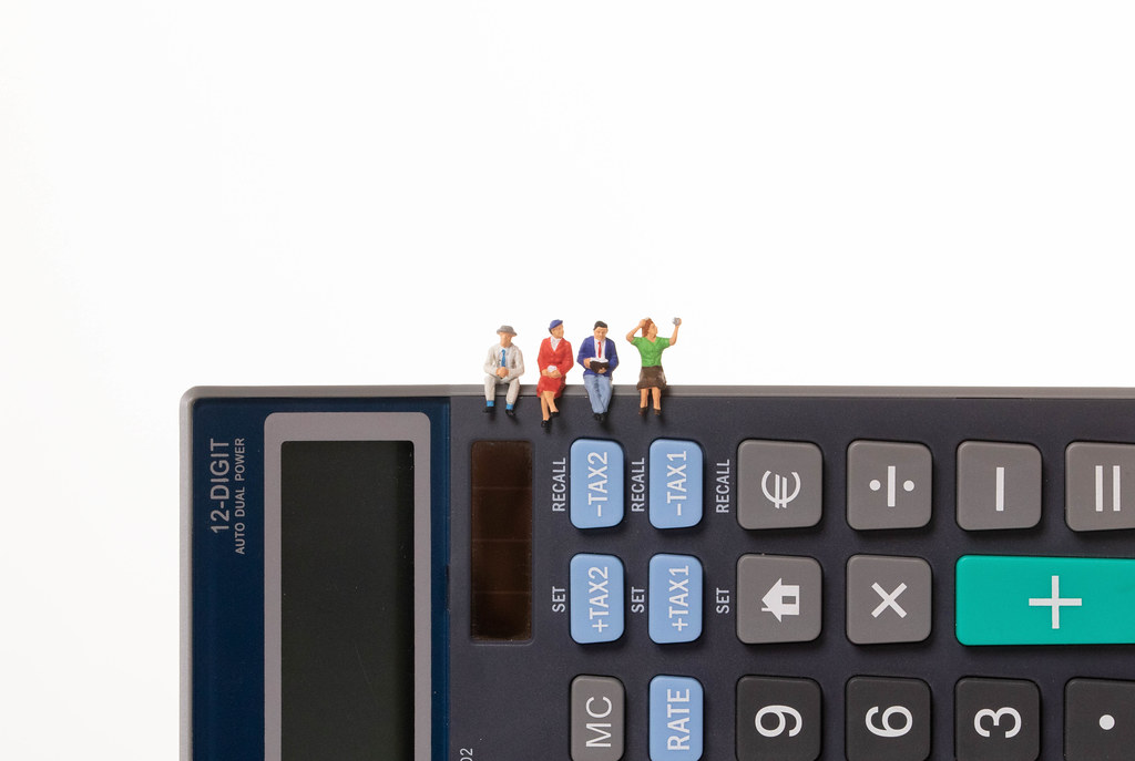 Group of people sitting on calculator with white background